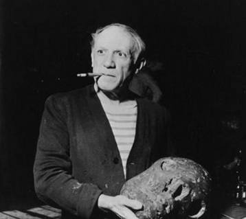Picasso smoking a cigarette looking at a large stone